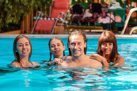 A group of three young caucasian women and one man pose while swimming in a pool. Stok Fotoğraf