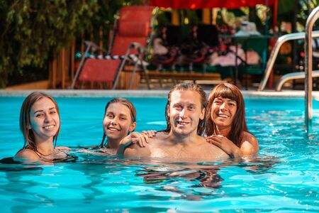A group of three young women and one man pose while swimming in a pool. Stok Fotoğraf