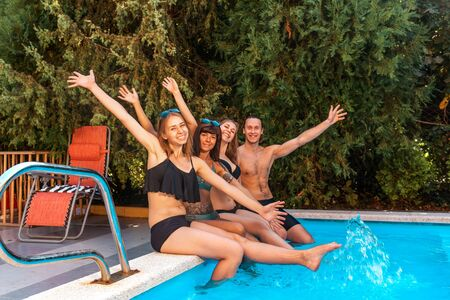 A group of three young women and one man, happily waving their arms and smiling, sitting on the edge of the pool