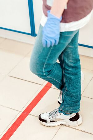 Person in medical gloves stand in red line, crossed legs close-up. Attention line on the floor of the store to maintain social distance. Concept of the coronavirus pandemic and prevention measures . 스톡 콘텐츠
