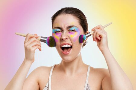 A young pretty woman with bright eyelid makeup, holds makeup brushes near her cheeks and screams. Yellow-pink background. Copy space. The concept of makeup, self-care and cosmetics.