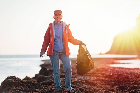 A young Caucasian female volunteer in a jacket holds a large garbage bag after cleaning the beach. In the background, the beach, the sea and the sunset.