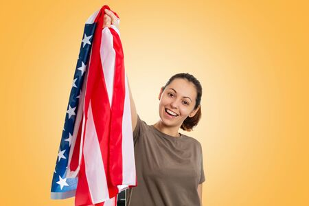 Caucasian happy woman with an American flag in her hands holds it up. Yellow background. The concept of patriotism, strength, freedom and sports fans. Foto de archivo