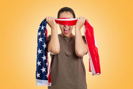 Emotion. Portrait of angry woman, screams and removes the American flag blindfold from her eyes. Yellow background. The concept of protest and patriotism. Foto de archivo