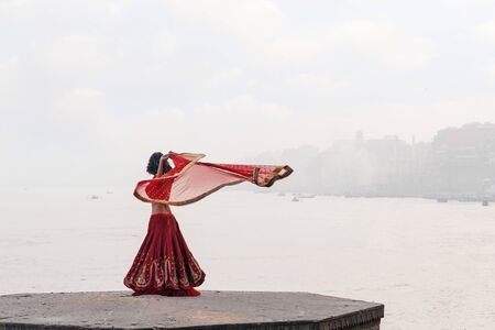 A beautiful Indian woman in a red Sari, dancing with a handkerchief in her hands, alone on the street. In the background, there is a river and a view of the city. Imagens