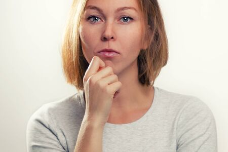 The concept of psychology and emotions. A young blonde woman leans her cheek on her hand, and looks thoughtfully. White background and close up.