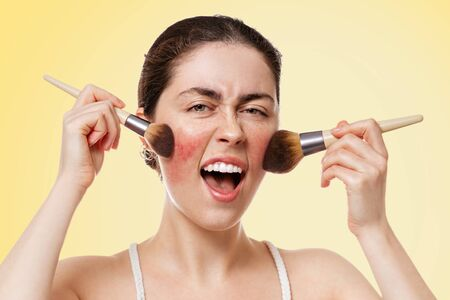 Portrait of young beautiful woman opens her mouth and expressively swings her makeup brushes over her Yellow background. The concept of makeup and rosacea.