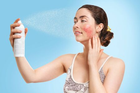A young Caucasian woman with rosacea on her cheeks sprays thermal water on her face, getting relief and freshness. Blue background. Concept of cosmetology, skin care and rosacea.