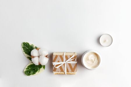 Cosmetics and self-care. A cotton flower with green leaves, handmade soap, a jar of cream and a candle are laid out on a white background. Flat lay and copy space. Banque d'images