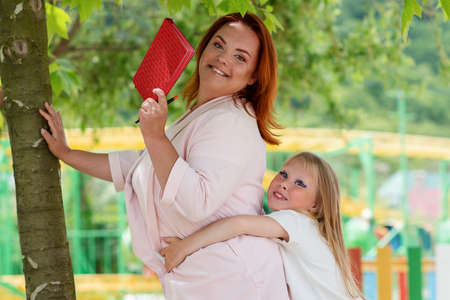 Preparation for school. A little Daughter hugs her mother from behind, who is holding a notebook in her hands. Upbringing and education of children.
