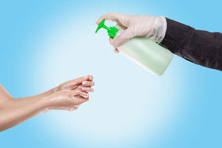 Hand washing.A man in medical gloves squeezes liquid soap on the hands of a woman who washes them with foam.Hands close-up.Blue background.Concept of antiseptic hand washing, disinfection and protection from bacteria and viruses. Banque d'images