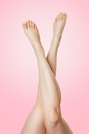 Smooth beautiful female legs crossed on a pink background. Copy space. Concept of cosmetology, removal of excess hair on the legs and beauty.