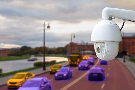 The concept of video surveillance and security technology. CCTV camera on the background of a road bridge with traffic in cloudy weather.