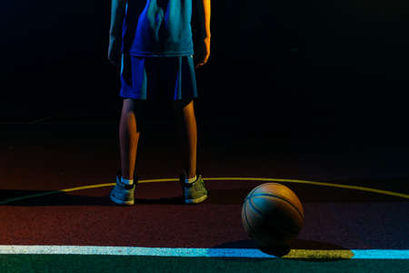 Basketball. A teenage boy in a blue sportswear stands on the Playground with ball. Close up of legs. Black background. Rear view. Concept of sports games.