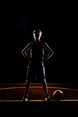 Basketball. The silhouette of a teenage Boy in blue sportswear confidently poses with his hands on his hips. The ball is on the ground. Black background. Concept of sports games. Reklamní fotografie