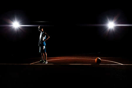 Basketball. The silhouette of a teenage Boy in a blue dress standing aside from a basketball. Black background with spotlights. Copy space. Concept of sports games.