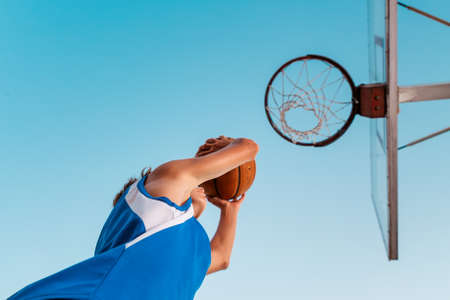 Basketball. A teenager in blue sportswear throws a ball into a basketball Hoop. Bottom view. Sky in the background. Concept of sports games.