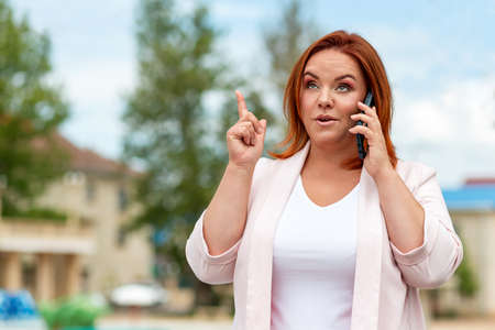 Communications. Portrait of a Beautiful Caucasian woman plus size, calling on the phone. Outdoor. Concept of business, freelancing and communication. 免版税图像