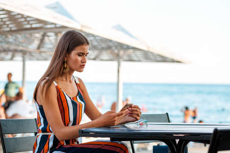 A woman with a serious look reads something on her phone. Summer cafe on the beach. A copy of the space. Business and online technology concepts.