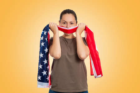 Emotion. Portrait of an angry woman tying her mouth with an American flag. Yellow background. The concept of protest and patriotism.