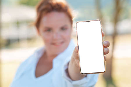 Communication and business. A woman holds a smartphone. Portrait in a blur. Mock up.