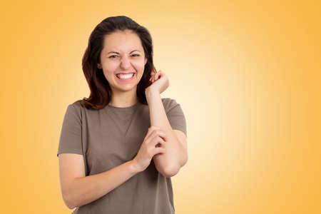 Scabies. Portrait of a Caucasian young woman scratching her hand. Yellow background. Copy space. Concept of allergies and skin diseases.