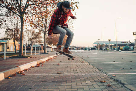 Skateboarding. A man does an Ollie stunt on a skateboard. Jump in the air. Street on the background.