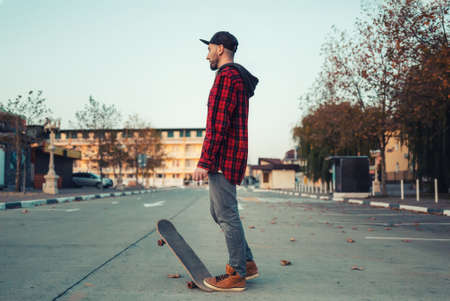 Skateboarding. A man poses with a skateboard. Street in the background.