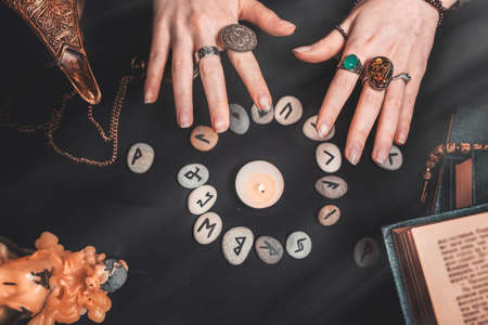 Astrology and esotericism. Female witch hands conjure over the rune circle. On a black background lie fortune-telling runes, a book, precious amulets, a copper lamp and a candle. Copy space.