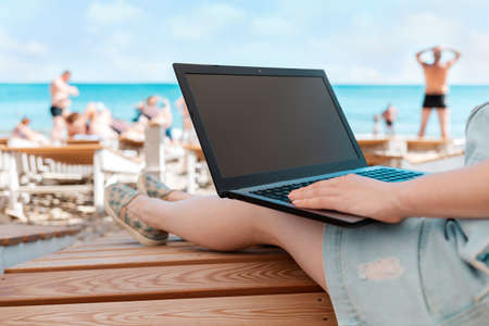 A person uses a laptop. In the background, the sea and the beach. The concept of freelancing and studying. Banco de Imagens