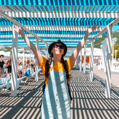 The summer and holidays. The happy woman raised her hands in joy. The striped shadow of the awning. Stockfoto