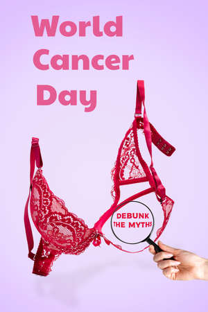 World cancer day. Pink lace bra on a lilac background and a woman's hand with a magnifying glass. Vertical orientation. Copy space. Debunk the myths.