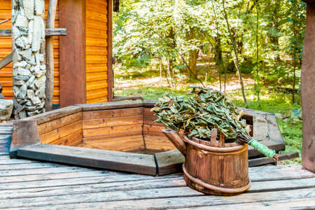 Bath and sauna. Wooden bathhouse with bucket and broom. Traditional hygiene. Outdoor.