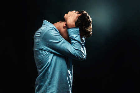 The concept of domestic violence. A teenage boy covers the back of his head with his scratched hands and hides his head. Profile view. Copy space.