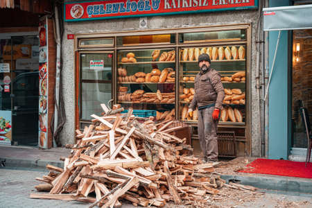 12/23/2019, Istanbul, Turkey. A man stands on the street next to a pile of firewood. In the background is the storefront of a bakery with bread.