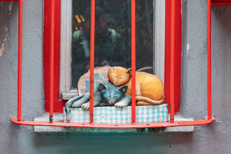 Decorative figure of two sleeping cats located behind the red bars at the window. Close up. Old streets of Istanbul, Turkey. The concept of street art.