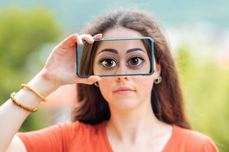 A woman closes her eyes with a smartphone, with a picture of huge cartoon eyes. The concept of hiding identity and fake pages in social networks.