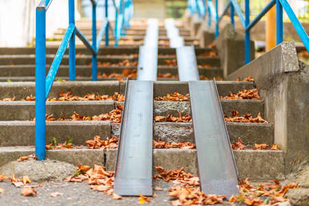 Steps with a blue railing and ramp, covered with autumn leaves. Bottom view. Nobody.