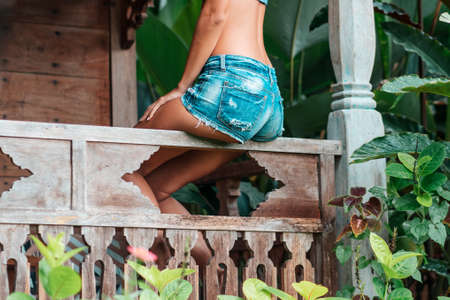 A tanned woman in summer clothes poses while sitting on the wooden railing of a house surrounded by tropical plants. Buttocks in denim shorts close-up. Summer vacation and travel concept. Foto de archivo