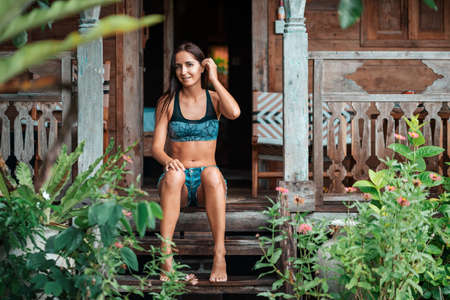 A beautiful tanned woman in summer clothes poses sitting on the wooden steps of a house, surrounded by tropical plants. Summer vacation and travel concept.