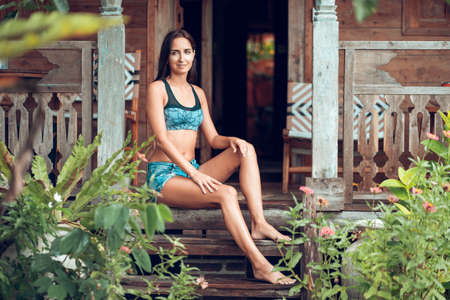 A beautiful slim tanned woman in summer clothes poses sitting on the wooden steps of a house, surrounded by tropical plants. Summer vacation and travel concept. Foto de archivo