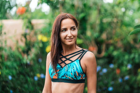 Hot summer. Portrait of a beautiful tanned, slender woman in a swimsuit poses in the refreshing tropical rain. Summer vacation and travel concept.