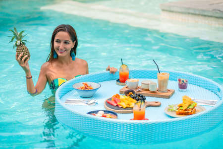 young, tanned girl standing in the pool near the Breakfast basket and holding a pineapple.