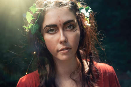 Fantasy. Portrait of a young brunette woman in the form of an elf, druid or fairy. Dark background in the background.