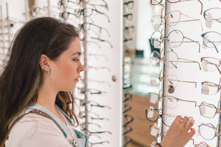 Health and vision. A young and pretty woman chooses glasses in the salon of optics.