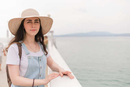 Portrait. A young pretty woman in a hat, leaning on the balustrade and posing for the camera. Archivio Fotografico