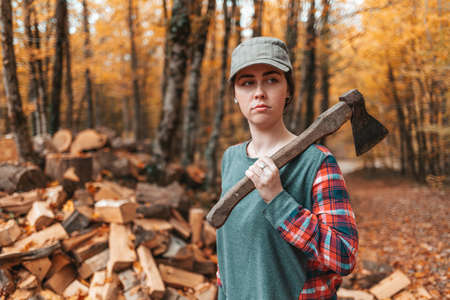 Preparation for the heating season. A young woman stands with an ax on her shoulder and looks gravely away. In the background, a pile of firewood and autumn forest.