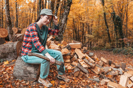 Preparation for the heating season. A young woman with an ax in her hands sits on a log and adjusts her cap on her head. In the background autumn forest.
