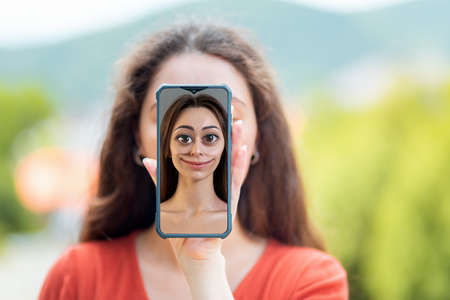 A woman covers her face with a smartphone with a cartoon portrait of a woman. The concept of hiding identity and fake pages in social networks.