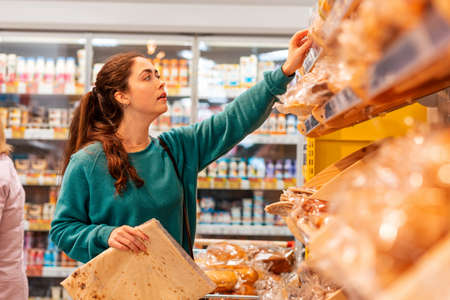 Portrait of a young Caucasian woman reaches for the package to the top shelf. Store shelves in a blur, in the background. The concept of buying goods and shopping.